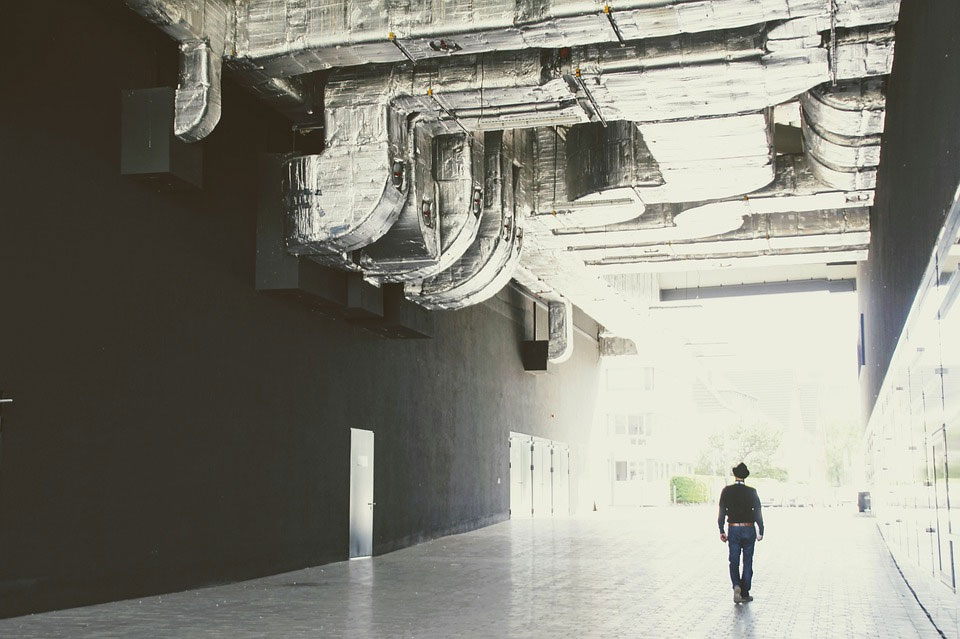 cooling capacity.man walking down a grey hallway with large metal ducts above him