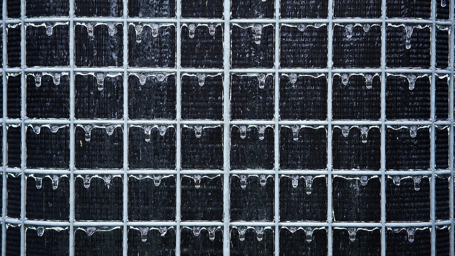 Close up of a metal grid with a black backdrop. Frozen water droplets hand on the edge of each metal rung.