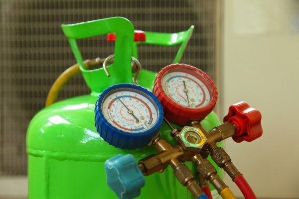 A neon-green canister filled with freon gas is hooked up to pressure gauges