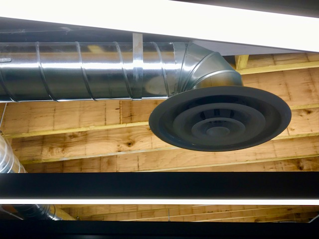 A forced air metal duct hanging from the ceiling. exposed timber is behind it.